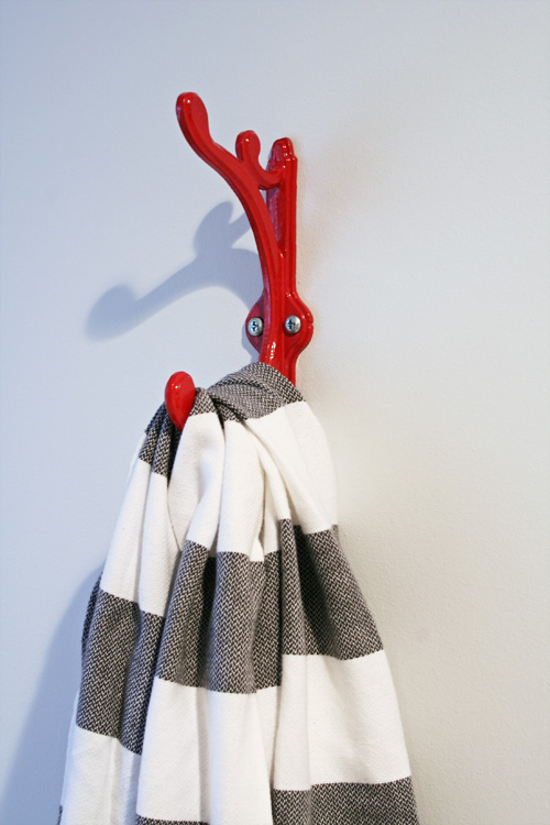A grey and white towel hangs from a red hook.