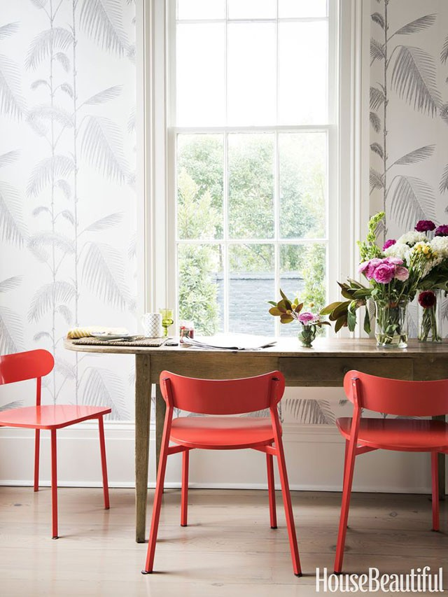 A Weathered Wooden Table with Modern Red Chairs from CB2