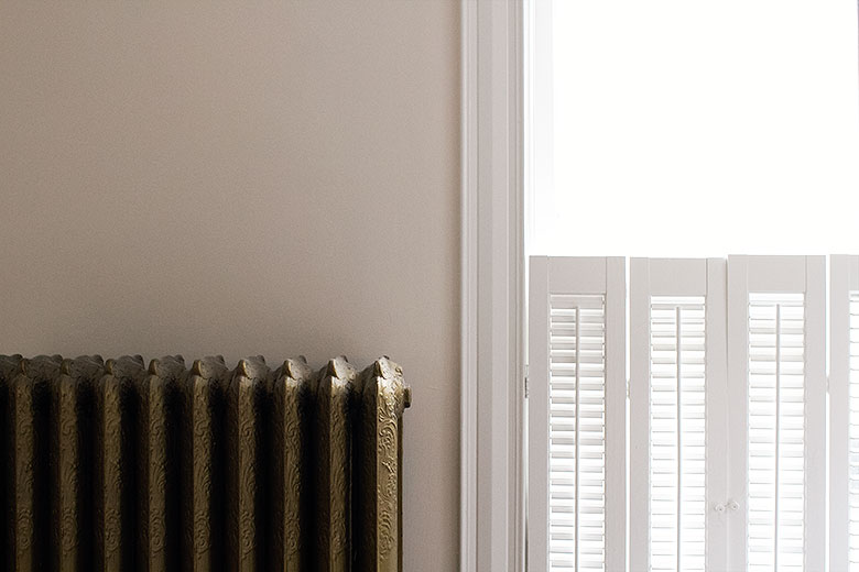 Antique Gold Cast Iron Radiator, Palest Blush Pink Walls, White Trim and Wooden Shutters