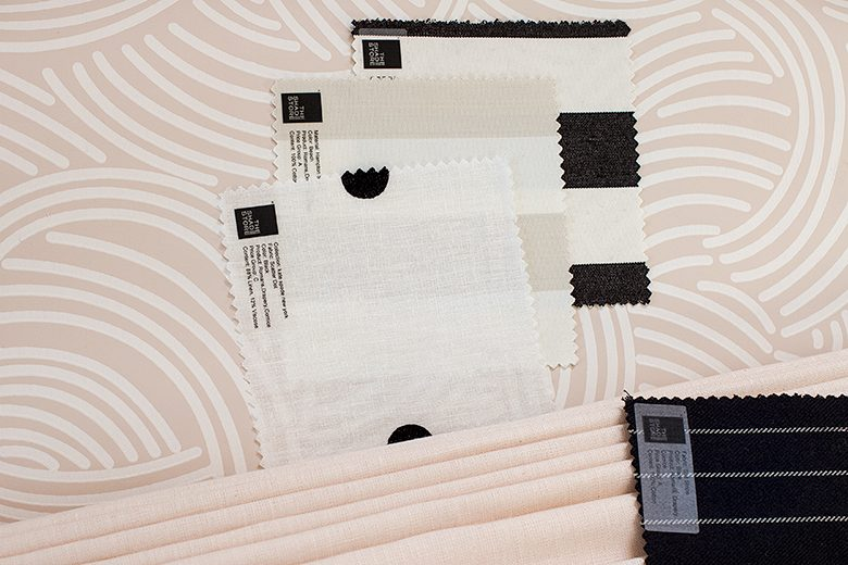 Fabric samples from The Shade Store against pink Tourbillon Farrow & Ball wallpaper