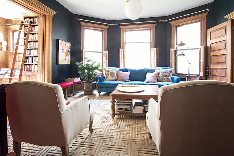 Living Room with Black Walls, Teal Sofa, and Annie Selke Rug